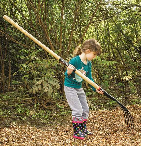 HILLSBORO TRIBUNE PHOTO: TRAVIS LOOSE - Four-year-old Annika Welch manages a pitchfork as she spreads bark chips at Jackson Bottom Wetlands Preserve. When asked why she came to the preserve, Welch said: 'Because it's helping the community.'