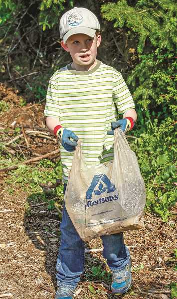 HILLSBORO TRIBUNE PHOTO: TRAVIS LOOSE - Farmington View Elementary student Evan Redmond, 9, picks up trash that collected along the edges of the preserve following winter flooding.  Picking up the trash, Evan said, will help save animals because styrofoam is really bad for them. Other volunteers referred to him as the Litter pick-up rock star.