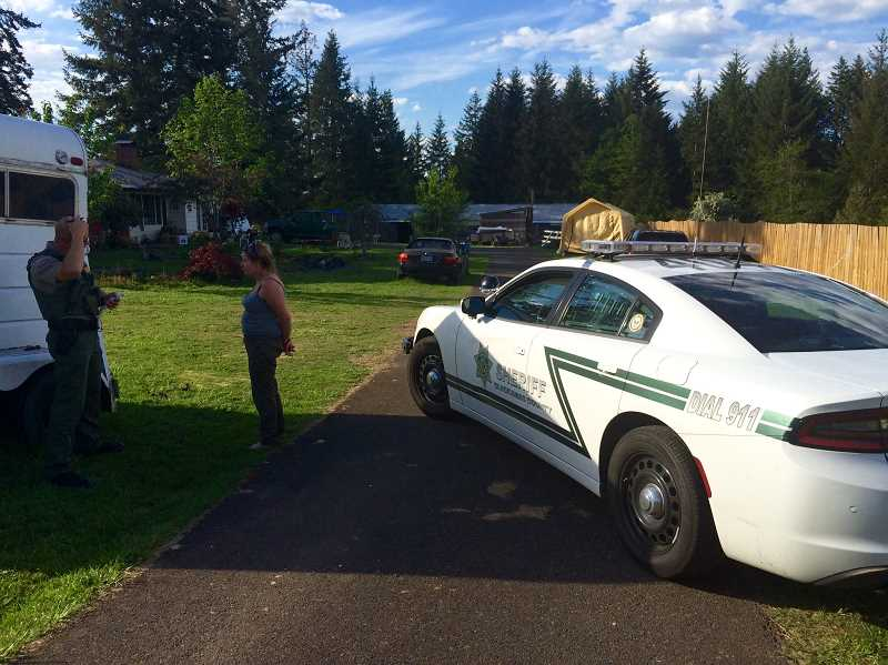 A Clackamas County Sheriffs deputy talks Monday afternoon to a handcuffed Lynn Hakala outside her home on Southeast George Road near Estacada. She is accused of firing shots during an argument with her daughters.