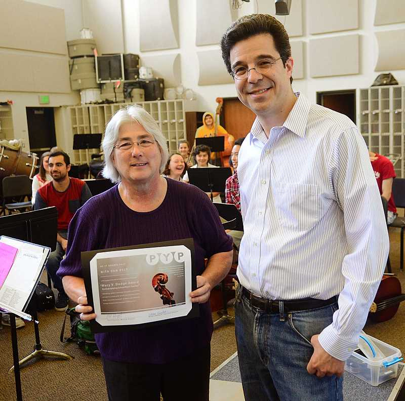 REVIEW PHOTO: VERN UYETAKE - Portland Youth Philharmonic musical director David Hattner presents Nita Van Pelt with the Mary V. Dodge Award for music educators Monday while her Lake Oswego High School orchestra class looks on.