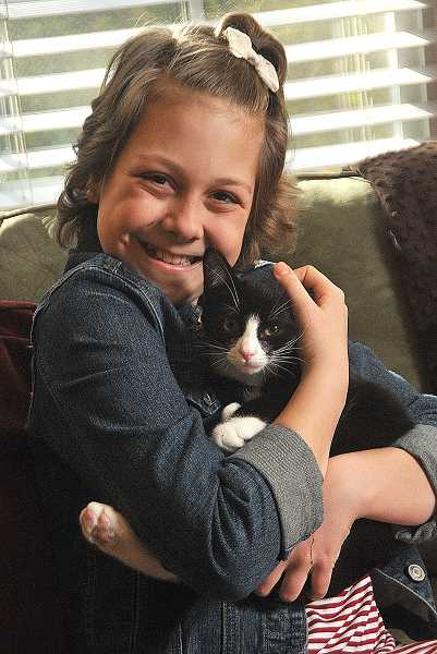 REVIEW PHOTO: VERN UYETAKE - Cancer survivor Anna Seely (shown here with her kitten, Oreo), a seventh-grader at Lakeridge Junior High, is The Review's Amazing Kid for 2016.