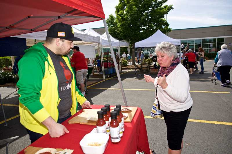 TIMES PHOTO: JAIME VALDEZ - Nanci Crum of Aloha tries a sample of Red Duck Ketchup from Michael Visenberg at the new Aloha Community Farmers'  Market.