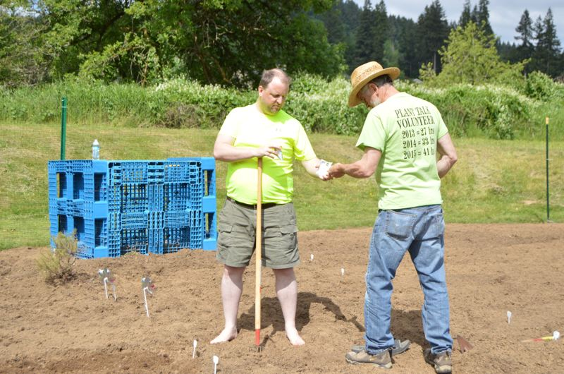 SPOTLIGHT PHOTO: NICOLE THILL - Craig Marquardo, property manager at Scappoose Creekside Apartments, and Leo Mock open packages of seeds to plant in a new community garden in the apartment complex, Monday, May 9.