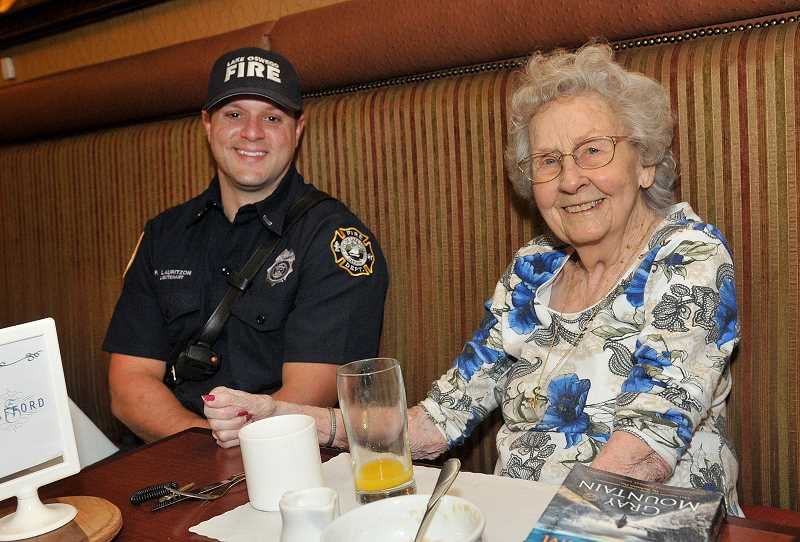 REVIEW PHOTO: VERN UYETAKE - LOFD Lt. Paul Lauritzon enjoys breakfast with resident Lea Eastin at The Stafford.