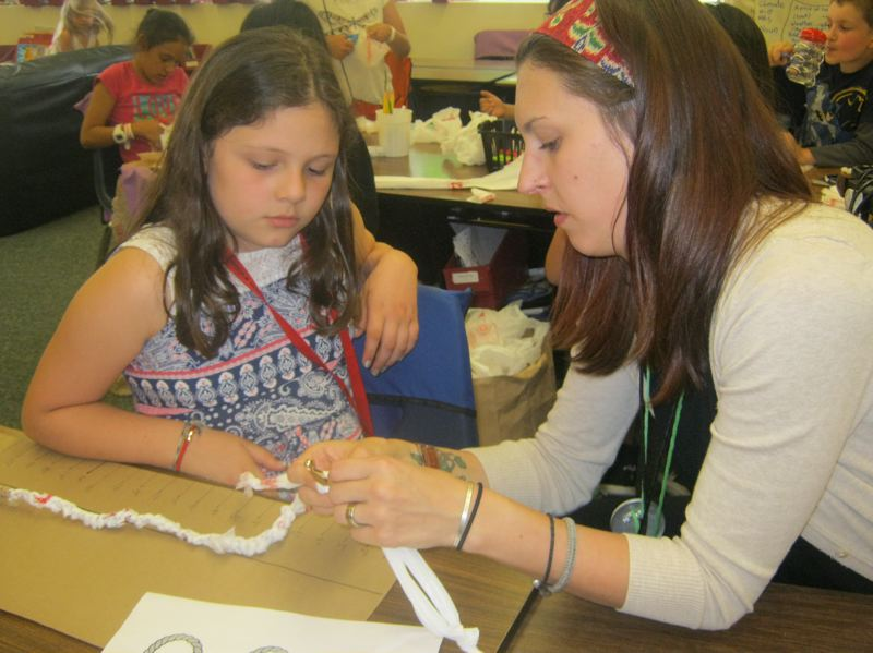 COURTESY PHOTO - AmeriCorp member Jordan Breasseale teaches third-grader Quetzaly Alvaradò Bravin the slip knot technique needed to crochet plarn into a sleeping mat as part of an after-school program at Margaret Scott Elementary School.