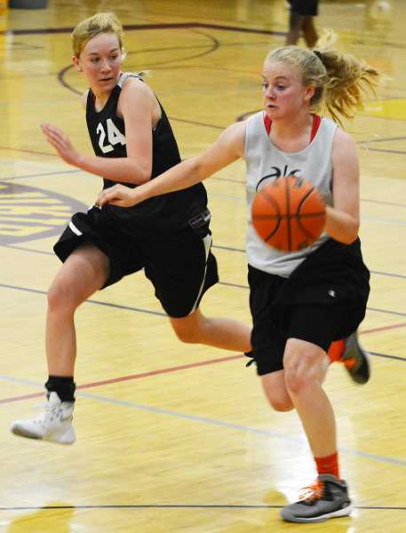 SPOTLIGHT PHOTO: JAKE MCNEAL - Lions sophomore guard Myranda Northrup (24) defends against Scappoose freshman guard Sara Mills in St. Helens' 41-38 win on Saturday, June 11, at Milwaukie High School.