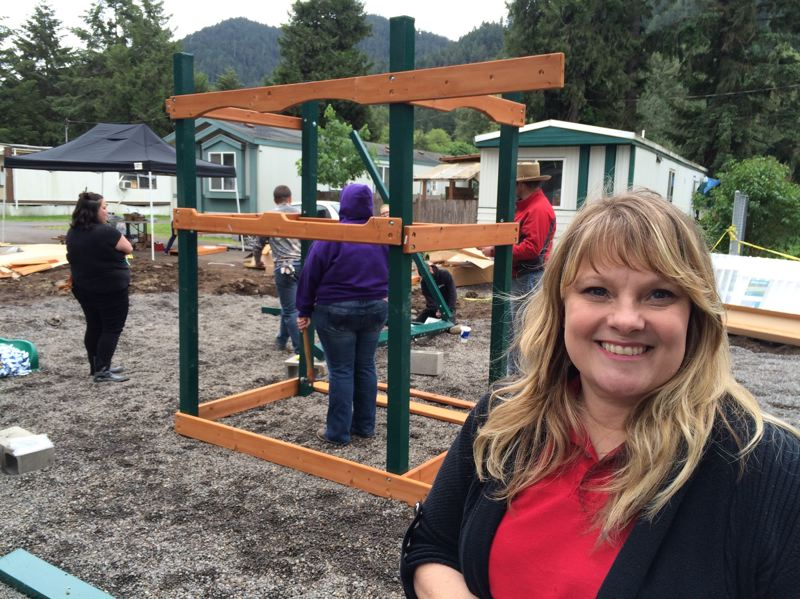 PHOTO COURTESY ST. VINCENT DE PAUL OF LANE COUNTY - Gienia Baines, director of social services for St. Vincent de Paul in Oakridge, works with volunteers from Home Depot to build new play structures at the Oakridge Mobile Home Park.