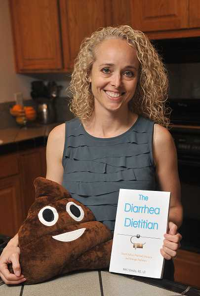 STAFF PHOTOS: VERN UYETAKE - Niki Strealy, the Diarrhea Dietitian, poses with a plush poop and copy of her book, The Diarrhea Dietitian: Expert Advice, Practical Solutions, and Strategic Nutrition.
