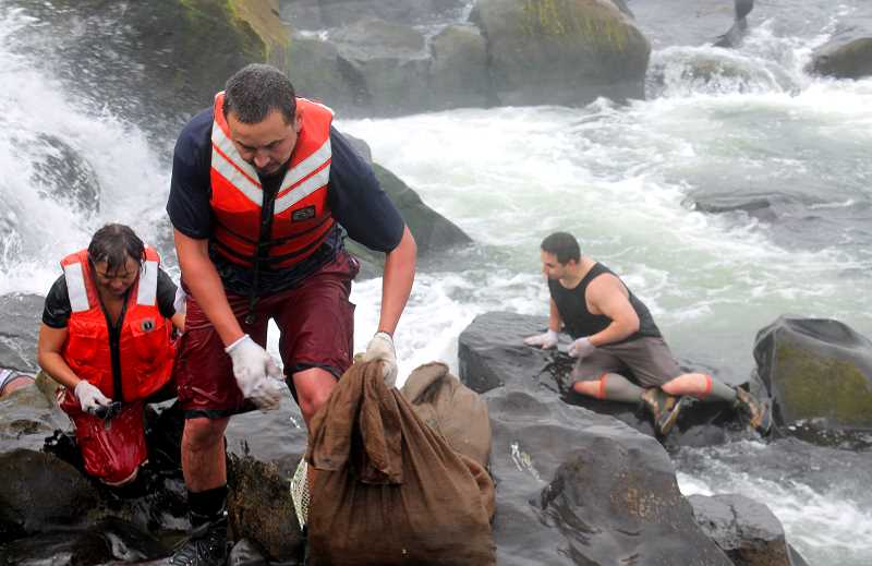 REVIEW PHOTO: PATRICK MALEE - Biologist Ralph Lampman lifts a bag full of lampreys onto the rocks. It was Lampman's first time participating in a harvest.