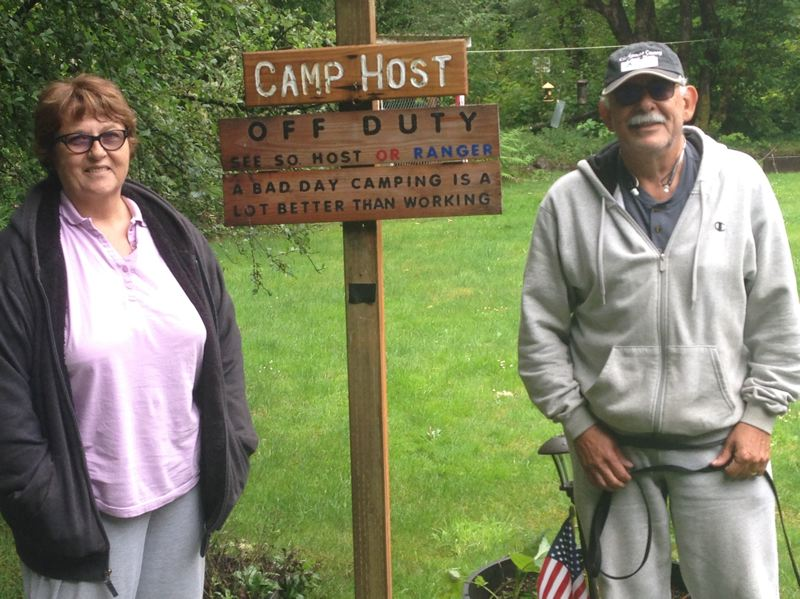 ESTACADA NEWS PHOTO: EMILY LINDSTRAND - Cathy and Allan Luna enjoy a day off from their duties as camp hosts at Metzler Park. The Lunas are passionate about camping, which is why the sign near their trailer says 'A bad day camping is a lot better than working.'