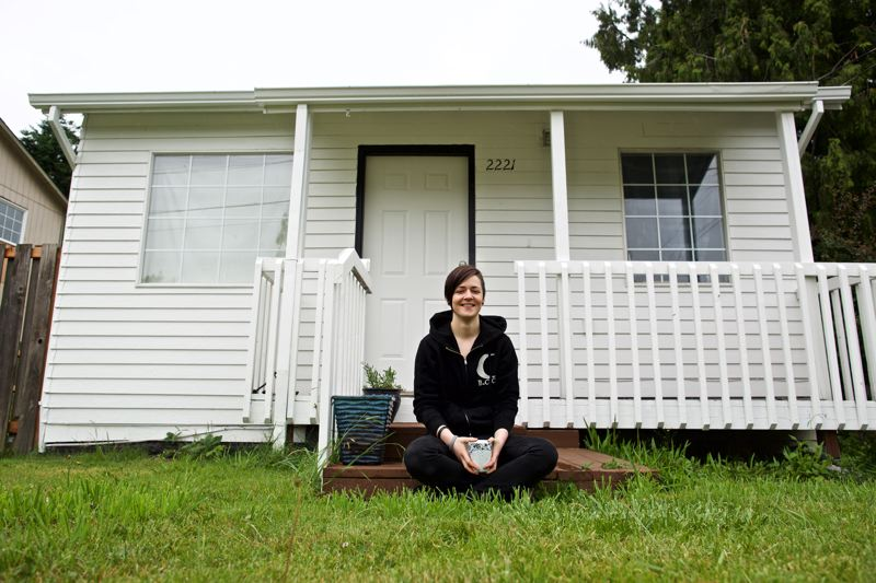 PORTLAND TRIBUNE: JAIME VALDEZ - Sara Forrest sits on the steps of her first home in East Portland. She was outbid for several other homes much farther away before being able to buy it.