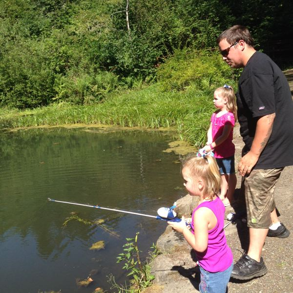 ESTACADA NEWS PHOTO: EMILY LINDSTRAND - Ray Shelnutt teaches his daughters Sarena and Sophia the basics of fishing at Small Fry Lake in Promontory Park.