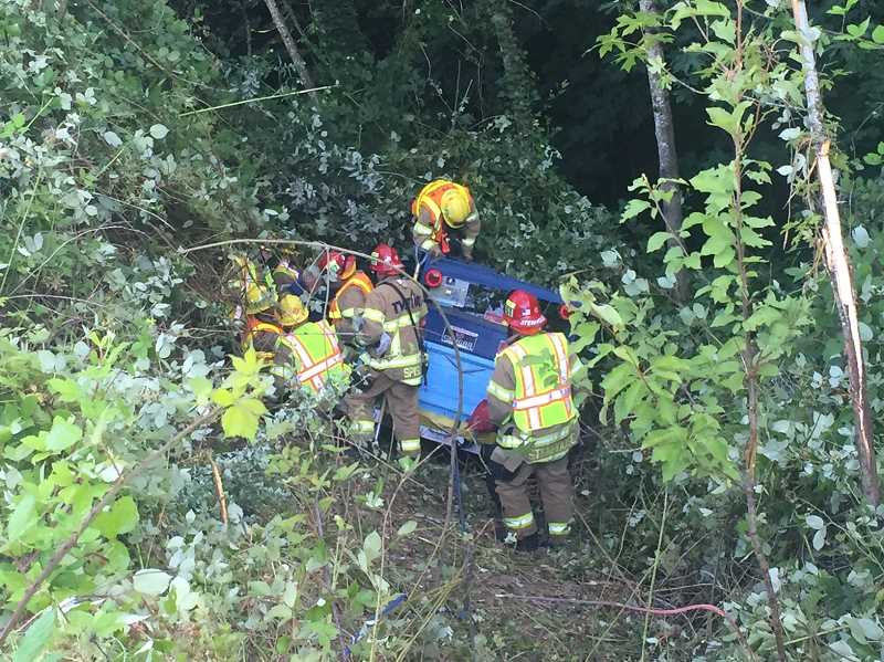 Tualatin Valley Fire & Rescue firefighters work to remove a man after his vehicle crashed down a steep embankment on Southwest Barnes Road on Thursday morning.