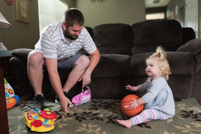 TIMES PHOTO: JOSH KULLA - Josh Fogarty of Troutdale plays with his daughter Peyton, who survived her struggle with CDH.