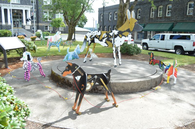 SPOTLIGHT PHOTO: NICOLE THILL - A collection of colorfully painted wooden dogs is on display in the St. Helens Courthouse plaza. Each dog was decorated by a local artist or business owner.