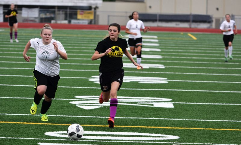 SPOTLIGHT PHOTO: JAKE MCNEAL - McKenna Coddington, right, an incoming St. Helens High School freshman, chases a lead ball in the Lions' 4-3 friendly defeat of Class 3A Rainier on Monday at St. Helens High.