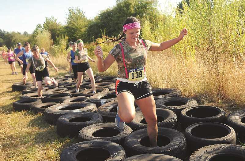 REVIEW FILE PHOTO: VERN UYETAKE - Jossilyn Blackman traverses the tire obstacle with ease during last year's 5K adventure run at Luscher Farm. This year's event, renamed Howl at the Moon, is scheduled for July 29.
