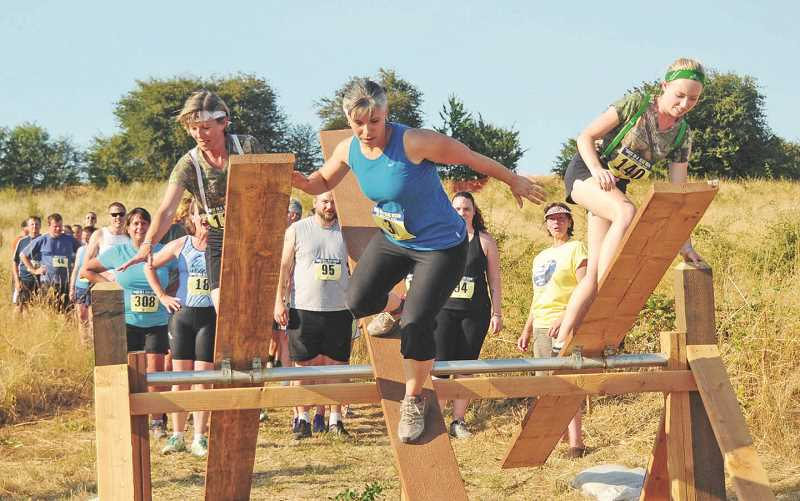 REVIEW FILE PHOTO: VERN UYETAKE - Runners take care as they traverse the teeter-totter, one of more than a dozen obstacles on the 5K course. Many of last year's favorite features will be back again next week.