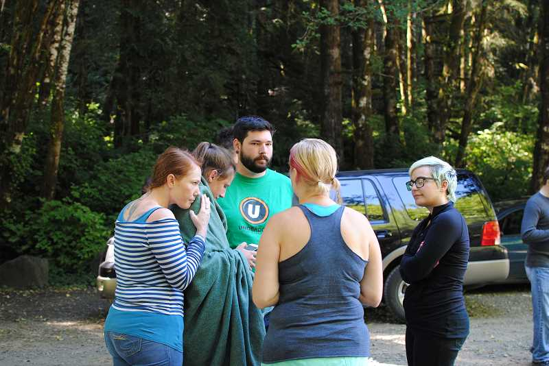 NEWS-TIMES PHOTO: JILL REHKOPF SMITH - Juliet Oglesbee (left) huddles against her niece, Emma Beggs, while Uncle Doug Beggs (green shirt) and Emmas mother (back to camera) share in the happiness of reuniting with the 13-year-old Aloha girl who got lost while going for a run near the Gales Creek Campground