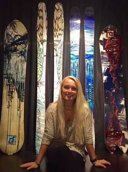SUBMITTED PHOTO - At the Geezer Gallery, Natalie Mussotto poses in front of one of her specialties - painting snowboards. Here they give the appearance of being a stained-glass window.