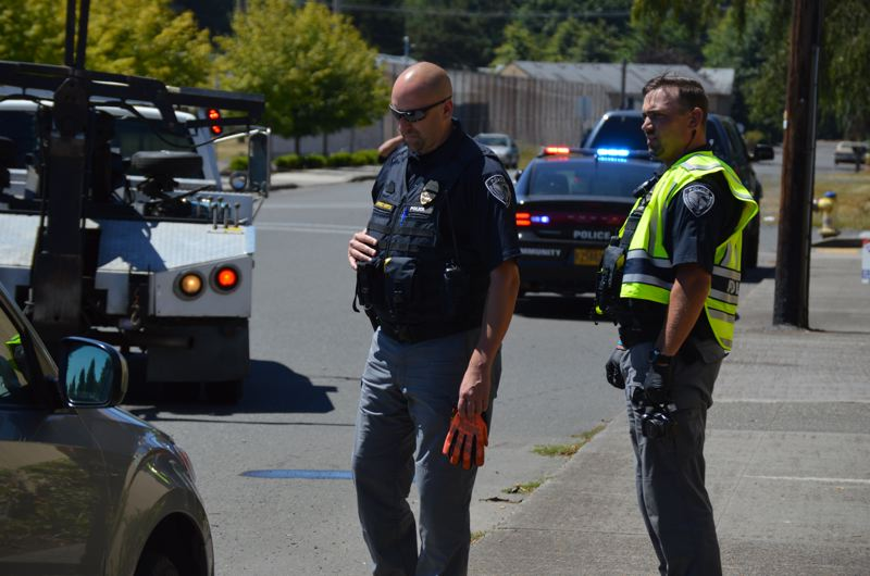 SPOTLIGHT PHOTO: COURTNEY VAUGHN - Scappoose Police Sgt. Dennis Viereck and Officer Matt Dorick respond to the scene of a crash Wednesday afternoon in Scappoose. The officers now wear lighter uniforms and use their first names to identify themselves, in an effort to connect better with the community they patrol.