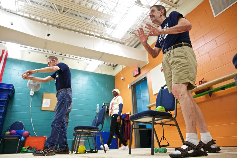 TIMES PHOTO: JAIME VALDEZ - Erv Schlichting, right, and his younger brother Ray, left, exercise at the Sherwood Regional Family YMCA, along with aide Wanjiru Nduku, center.