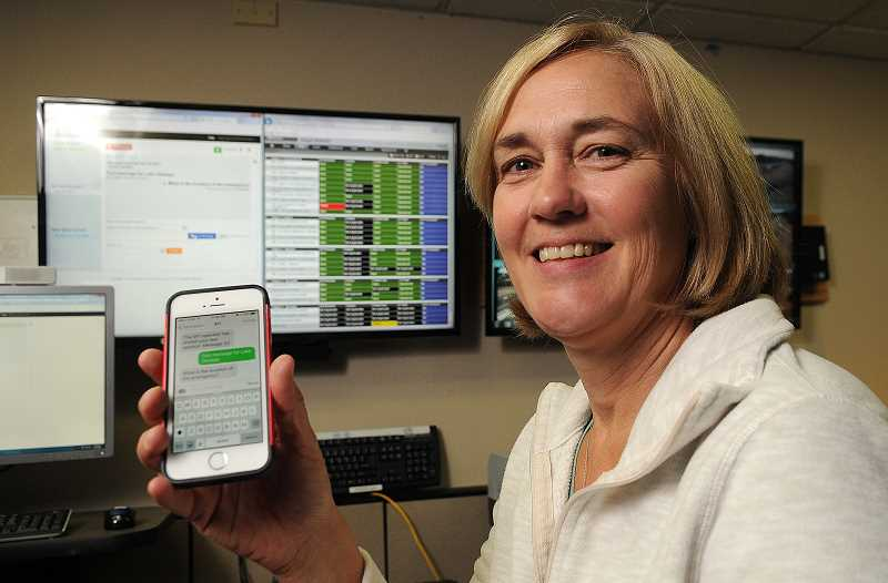 REVIEW PHOTO: VERN UYETAKE - Leslie Taylor, director of Lake Oswego's emergency communications center, demonstrate the new text-to-911 service. For users, communication with emergency dispatchers will be just like any other texting conversation.