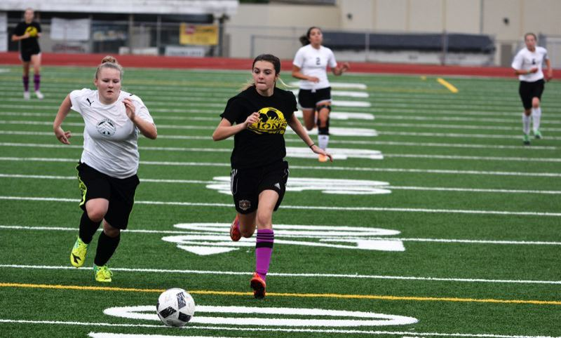SPOTLIGHT FILE PHOTO: JAKE MCNEAL - Incoming freshman McKenna Coddington, right, chases a lead ball in the Lions' 4-3 friendly defeat of Class 3A Rainier on Monday, July 18, in St. Helens.