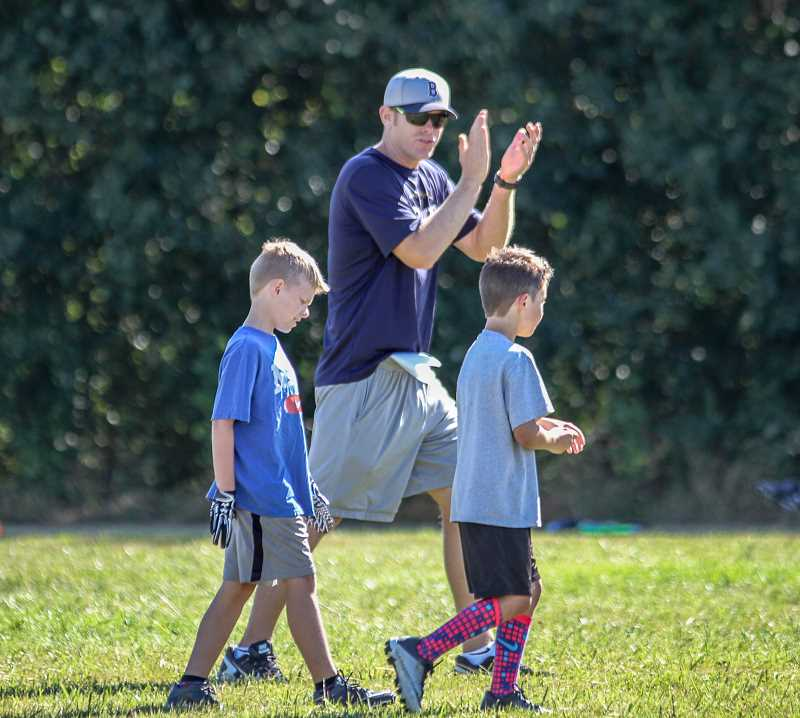 NEWS-TIMES PHOTO: WADE EVANSON - First year varsity football coach Cole Linehan provides encouragement to a couple local kids during the Little Guy Youth Camp in Banks.