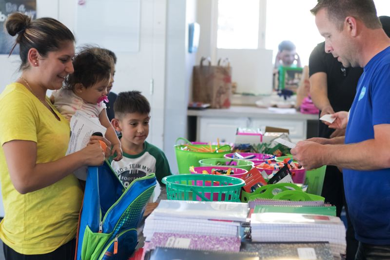 TIMES PHOTO: JONATHAN HOUSE - Gabbi Hernandez, with her daughter Riley and son Miguel, gather free school supplies at CPAH's annual giveaway.