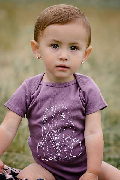 SUBMITTED PHOTO: LAURA AERNE - This new onesie from Carved Life comes in purple or Pacific blue and offers a choice of six designs. It's made from 100-percent organic cotten and will be available in September.