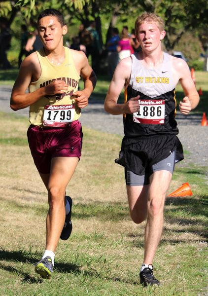 PAMPLIN MEDIA PHOTO: JIM BESEDA - Milwaukie junior Juan Gudino, left, and Lions senior Ben Johnstun, right, contend for third place less than a mile from the finish line at the Northwest Oregon Conference Preview on Wednesday at Blue Lake Park in Gresham.