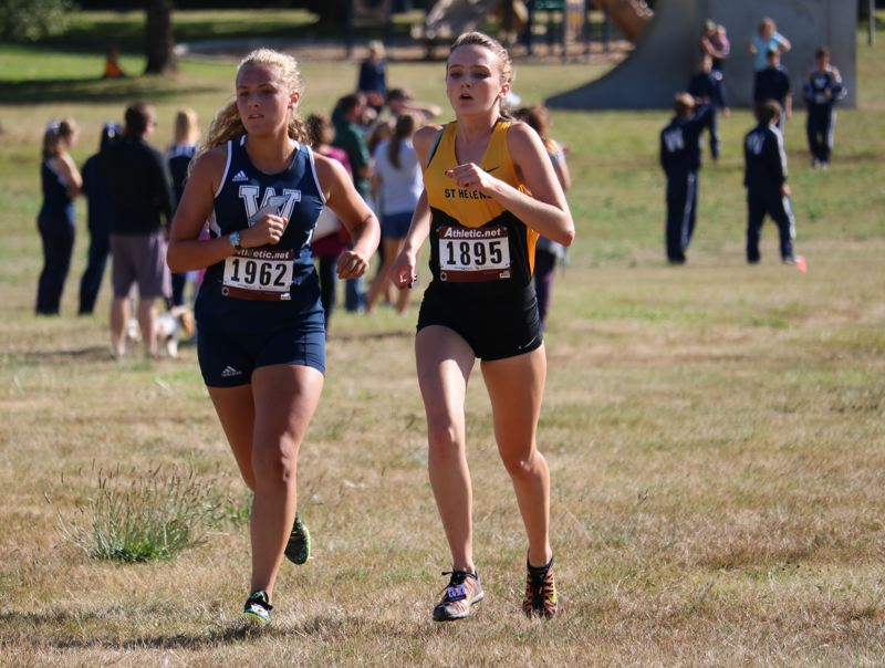 PAMPLIN MEDIA PHOTO: JIM BESEDA - Wilsonville senior Haley Prusse and Lions senior Josie Hanna race for second in the Northwest Oregon Conference Preview on Wednesday at Blue Lake Park in Gresham.