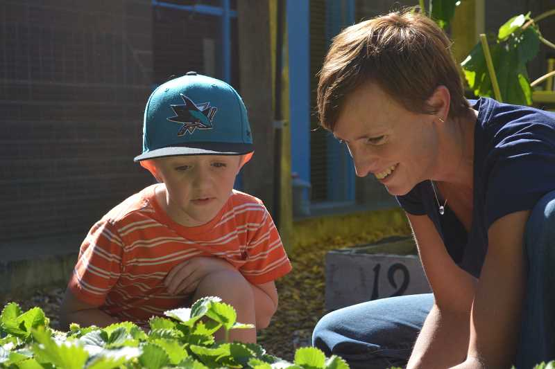 SUBMITTED PHOTO: HEATHER WICK - First-grade teacher Kristi Lunde and her student, Will Paquette, peer into a garden bed.