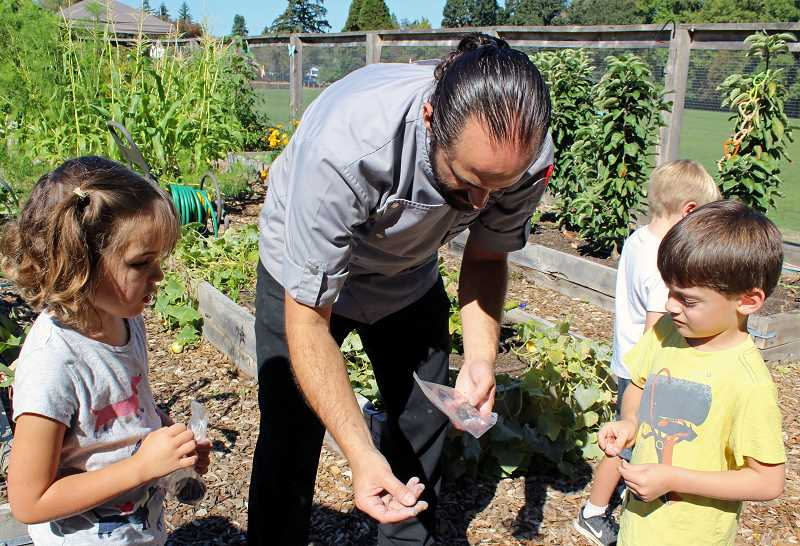 REVIEW PHOTO: JILLIAN DALEY - Chef Chris Starkus teaches kindergartners Lily Alvarez (left) and Mercury Karls about seed bombs.