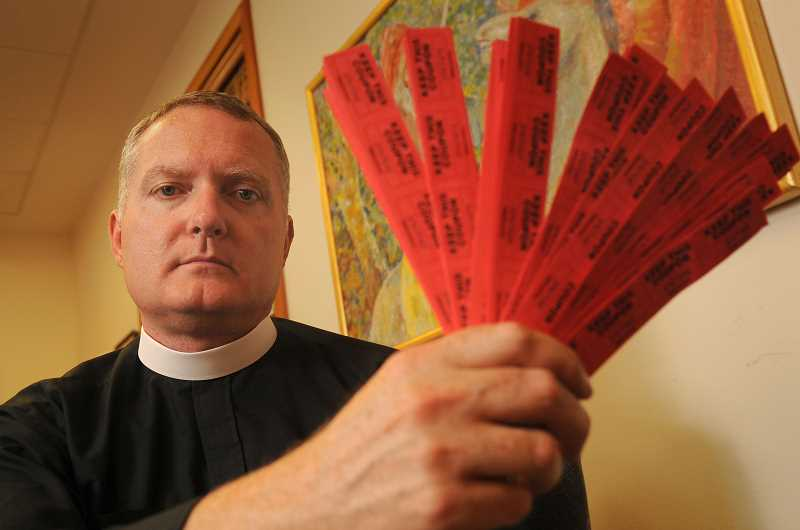 REVIEW PHOTO: VERN UYETAKE - The Rev. Jeremy Lucas of Christ Church Episcopal Parish in Lake Oswego holds the 150 tickets he purchased in an all-star softball team's raffle in July. The prize was an AR-15 assault rifle that Lucas said he would have transformed into a piece of art, but the pastor's handling of the weapon after taking possession came under investigation by the Oregon State Police.