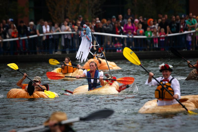 TIMES FILE PHOTO - Charity Marshall, center, guides her Wicked Witch pumpkin during Tualatin's annual Pumpkin Regatta last year.