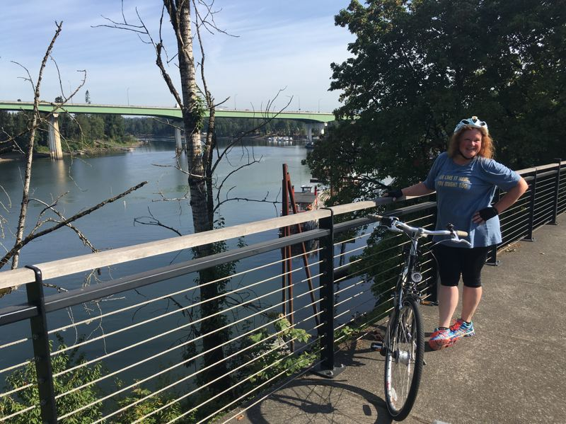 PHOTO BY ANYI WONG-LIFTON - Shelley Batty takes a quick break on the path off Highway 99E overlooking the Willamette River, on the way back to the Bike Concierge office.