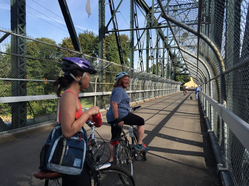 PHOTO BY BEVERLY WONG - Reporter Anyi Wong-Lifton (left) and Shelley Batty (right), co-owner of the Bike Concierge on the bridge over the Clackamas River near High Rocks City Park.