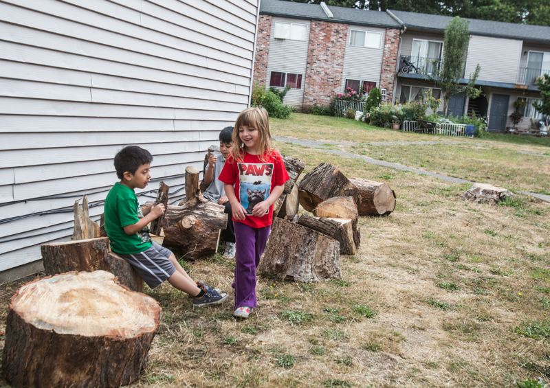 TIMES PHOTO: JONATHAN HOUSE - The children of Tigardville Apartments play with the cut-up remnants of a tree that used to stand in the middle of their commons.