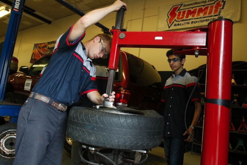 TIMES PHOTO BY JONATHAN HOUSE - Aloha High auto technologies student Ben Friant retreads a tire ahead of a class tour from U.S. Rep. Suzanne Bonamici.