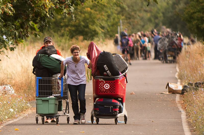 PAMPLIN MEDIA GROUP: JOSH KULLA - Homeless campers haul their belongings along the Springwater Corridor Trail Sept. 1 as the city of Portland began a wide-ranging cleanup of camps along portions of the trail.