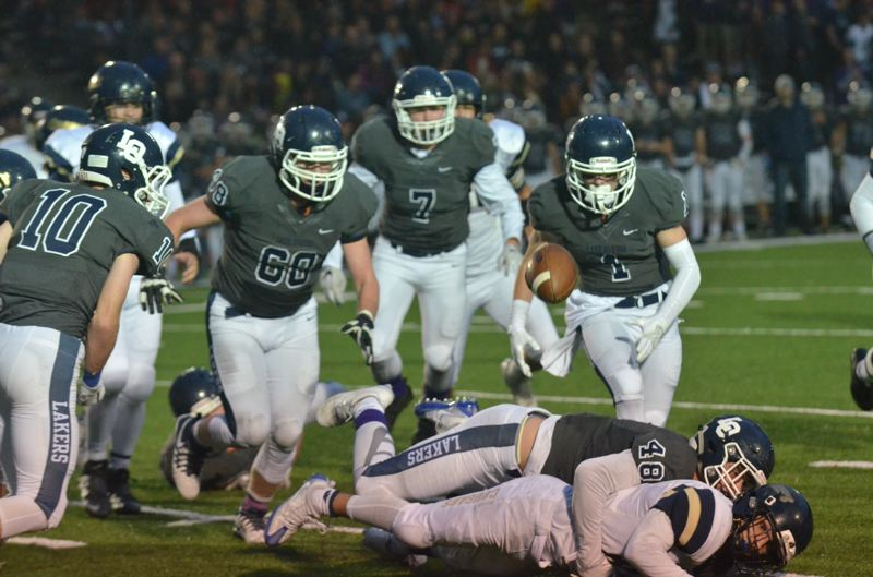 COREY BUCHANAN - Lake Oswego defenders chase a fumble during the teams victory over Canby last week.