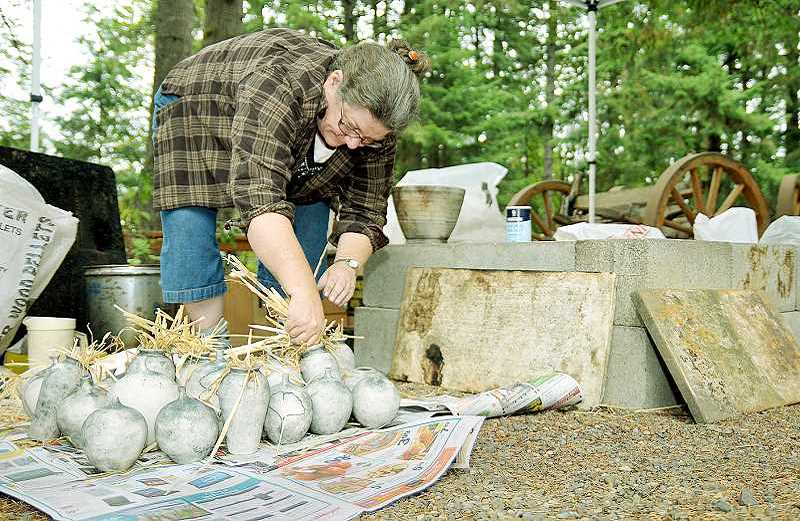 NEWBERG GRAPHIC / GARY ALLEN - Local pottery artist Linda Workman-Morelli displays a method of primitive firing to create her artwork, which she demonstrated during the 2015 Art Harvest Studio Tour.