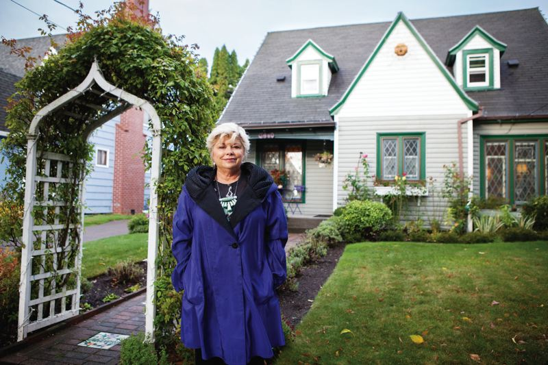 PORTLAND TRIBUNE: ADAM WICKHAM - Barbara Bushell stands in front of her home on Southeast Peacock Lane. She's spearheading efforts to get the lane, known for its annual Christmas light display and for its cluster of English Tudor-style homes, established as a historic district.