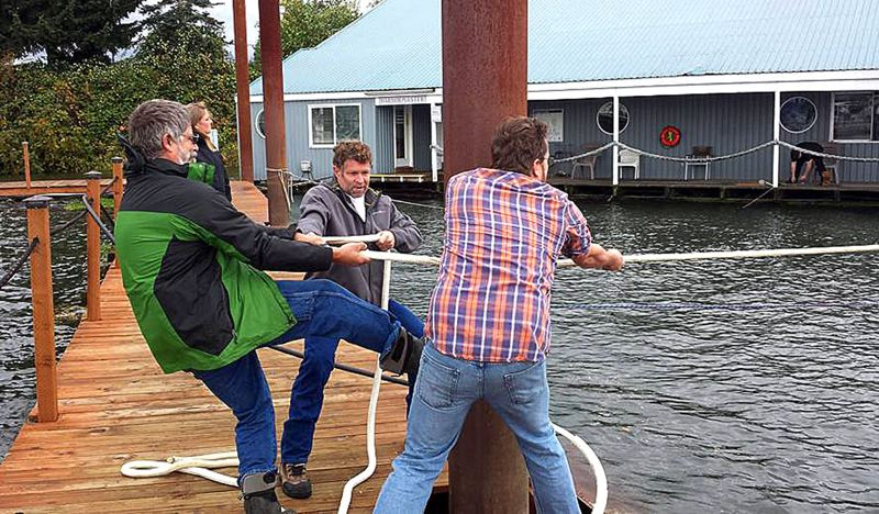 COURTESY PHOTO: GREGG TOWNSLEY - Several people grabbed a large rope and began pulling McCuddy's Marine building (in the background) back to its dock at the Columbia River's Multnomah Channel in Scappoose after the large building broke free of its moorings in the high wind and rough water.