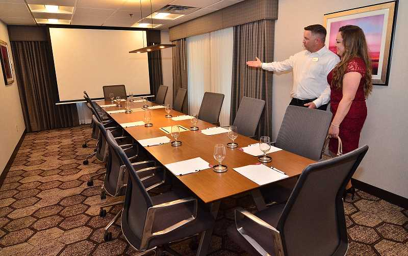 REVIEW PHOTO: VERN UYETAKE - Chief Engineer Brian Evanoff shows the Oswego Board Room to a guest at last week's unveiling of renovations to the Crowne Plaza hotel.