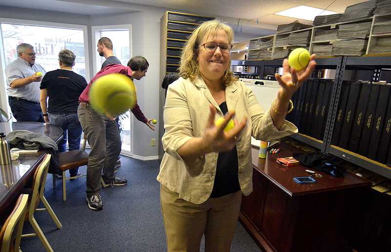REVIEW PHOTO: VERN UYETAKE - Leslie Pugmire Hole, editor of the West Linn Tidings and Wilsonville Spokesman, tries to juggle tennis balls during a Coaching Peace empathy workshop Oct. 20 designed to draw staff members together.