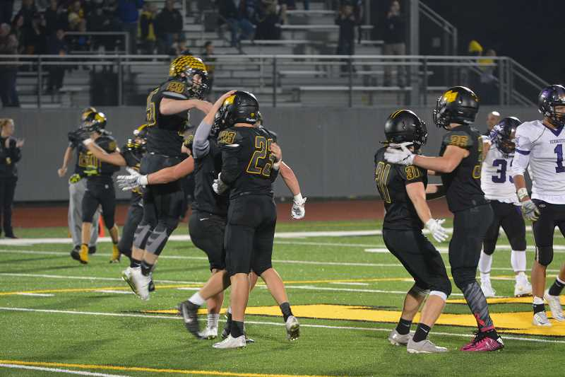 SPOTLIGHT PHOTO: JAKE MCNEAL - Tucker Mosley (25), Mason Rask, Austin Dragoo (31) and Dylan Brady (36) celebrate the win after Colton Beisley (23) deflects a pass over the middle as time expires.