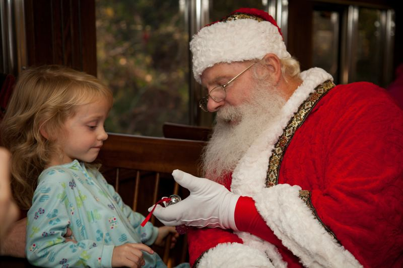 COURTESY: LOU HAMMOND GROUP - Santa gives a child a silver bell that symbolizes belief aboard The Polar Express.